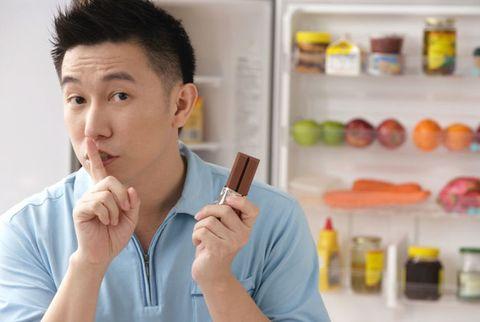 man sneaking a chocolate bar