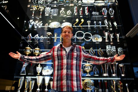 Sebastian Vettel of Germany poses next to the Infiniti red Bull Racing trophy cabinet during a visit to the Red Bull Racing Factory