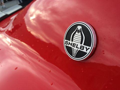 Motor vehicle, Red, Logo, Symbol, Hood, Emblem, Classic car, Trademark, Graphics,