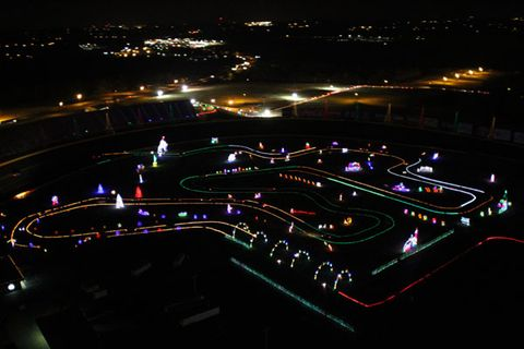 """<a href=""""https://www.youtube.com/watch?v=rp8lwpvQEIM"""" target=""""_blank"""">Clark Griswold's house</a> has nothing on Charlotte Motor Speedway. <br /><br /> Back in October, work crews at the track began unpacking four semi trucks full of Christmas lights. This LED arsenal—three million lights and 800 displays—is the main attraction at Speedway Christmas, an event that drew an estimated 150,000 visitors last year. If you think it took a while to hang the lights on your house, consider that this edifice required 2,700 man-hours of stringing and testing. <br /><br /> The appeal is twofold. First, there's the spectacle of thousands of lights flickering along to """"<a href=""""https://www.youtube.com/watch?v=yXQViqx6GMY"""" target=""""_blank"""">All I Want for Christmas is You</a>."""" And while that's happening, you're driving around the track of a hallowed NASCAR superspeedway ( tune your car's FM radio to get the music). There are periodic sets of cones to prevent Cale Yarborough wannabes from running 120 mph through Turn 4, but between the cones you can creep up the banking a little bit and get a feel for what it might be like out here in the heat of battle. Except, you know, you're in your own car, driving clockwise and listening to Mariah Carey. <br /><br /> The total course runs 3.1 miles. Drivers had down onto the infield road course and then back out under the bleachers, where the density of dancing lights makes you feel like you're driving through the Freemont Street Experience. The road course winds through the majority of the displays, which this year include a giant kissing Santa and Mrs. Claus who usher you off the oval and onto the infield. <br /><br /> About halfway through, you can take a break at the Christmas Village. This is a good opportunity to get out of the car, stretch your legs, and ride a camel. Or pet a goat. Or get some candy, or ride aboard a small train. Alternately, you can sit in your car and watch clips from Christmas movies (including <em>National Lampoon's """