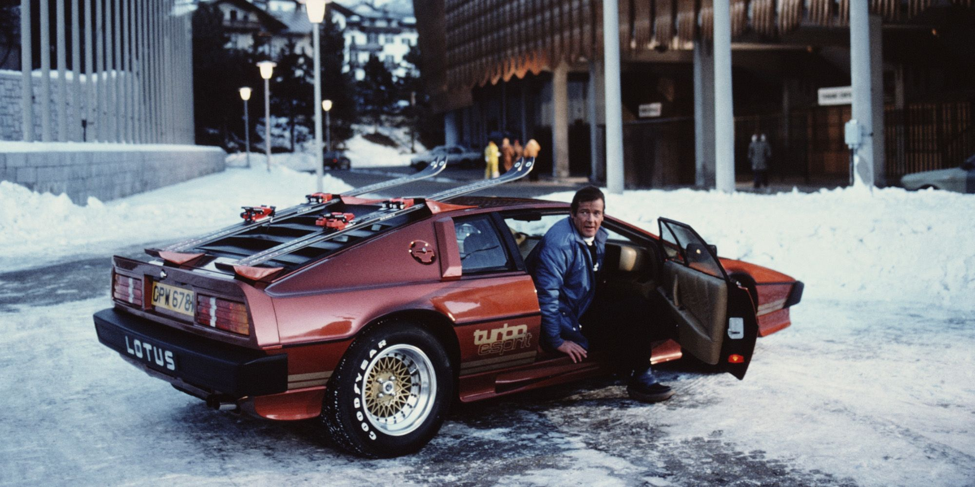 English actor Roger Moore poses as 007, with a Lotus Esprit Turbo, on the set of the James Bond film 'For Your Eyes Only' in Cortina d'Ampezzo, Italy, March 1981. (Photo by Keith Hamshere/Getty Images)