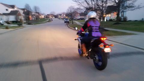 Motorcycle, Mode of transport, Road, Motorcycle helmet, Automotive lighting, Neighbourhood, Road surface, Helmet, Fender, Asphalt,
