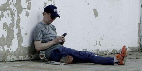 Cap, Blue, Human body, Denim, Jeans, Sitting, Elbow, Wine glass, Baseball cap, Drinkware,