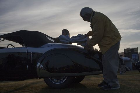 After driving onto the fairway, at the Lodge at Pebble Beach, Louis and Abigail Natenshon perform at external clean of their 1937 Peugeot 402 Pourtout Cabriolet. The Nathenshon's are from Highland Park, Ill. Every year, the world's auto enthusiasts travel to the Monterey Peninsula to participate in the Car Week that culminates with the luxurious Concours d'Elegance classic car competition.   PHOTOGRAPHED SUNDAY AUGUST 16, 2015 (Photo by Don Kelsen/Los Angeles Times via Getty Images)