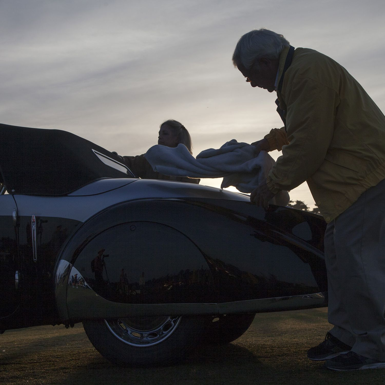 After driving onto the fairway, at the Lodge at Pebble Beach, Louis and Abigail Natenshon perform at external clean of their 1937 Peugeot 402 Pourtout Cabriolet. The Nathenshon's are from Highland Park, Ill. Every year, the world's auto enthusiasts travel to the Monterey Peninsula to participate in the Car Week that culminates with the luxurious Concours d'Elegance classic car competition. PHOTOGRAPHED SUNDAY AUGUST 16, 2015(Photo by Don Kelsen/Los Angeles Times via Getty Images)