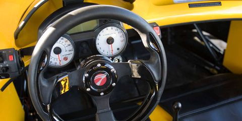 Motor vehicle, Mode of transport, Yellow, Steering wheel, Steering part, Automotive design, Speedometer, Gauge, Orange, Tachometer,