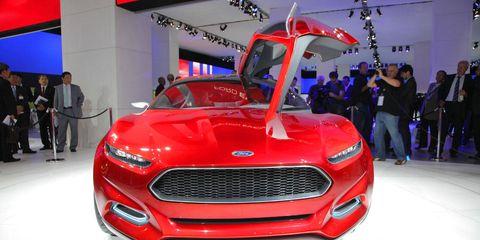 Motor vehicle, Automotive design, Event, Grille, Red, Car, Headlamp, Exhibition, Auto show, Logo,