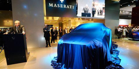 Automotive design, Event, Auto show, Exhibition, Logo, Vehicle cover, Luxury vehicle, Concept car, Hall, Display device,