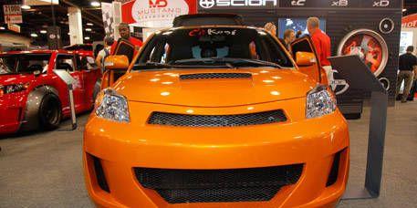 Motor vehicle, Automotive design, Vehicle, Land vehicle, Yellow, Orange, Car, Automotive lighting, Exhibition, Auto show,
