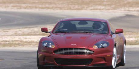 Automotive design, Vehicle, Hood, Car, Red, Grille, Road surface, Asphalt, Sports car, Automotive mirror,