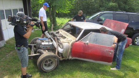 Video camera, Camera, Classic car, Fender, Cap, Automotive tire, Camera operator, Videographer, Television crew, Vehicle door,