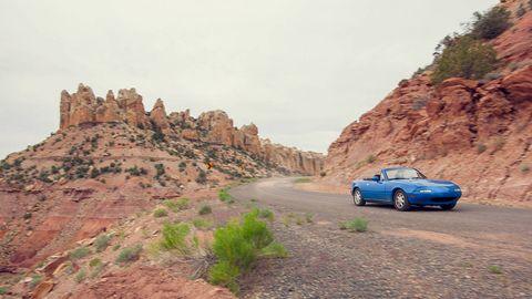 Mountainous landforms, Road, Automotive design, Car, Automotive mirror, Rock, Outcrop, Bedrock, Automotive parking light, Terrain,