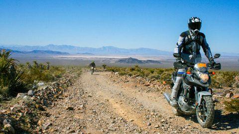Motorcycle, Automotive tire, Soil, Motorcycle helmet, Fender, Motorcycling, Auto part, Trail, Dirt road, Mountain range,