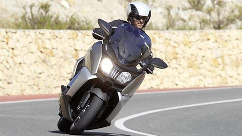 Motorcycle, Automotive design, Road, Motorcycle helmet, Road surface, Asphalt, Helmet, Personal protective equipment, Automotive lighting, Fender,