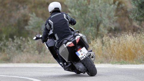 Motorcycle helmet, Motorcycle, Helmet, Road, Personal protective equipment, Asphalt, Motorcycling, Shoe, Road surface, Sports gear,