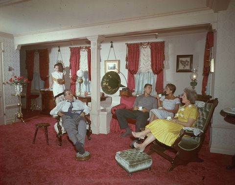 circa 1955: American cartoonist and film producer Walt Disney (1901-1966) sits with his family while they read and drink tea or coffee in a turn-of-the-century interior, possibly at Disneyland, California. L-R: His daughter, Diane, Disney, an unidentified man, his daughter, Sharon, and his wife, Lilly.