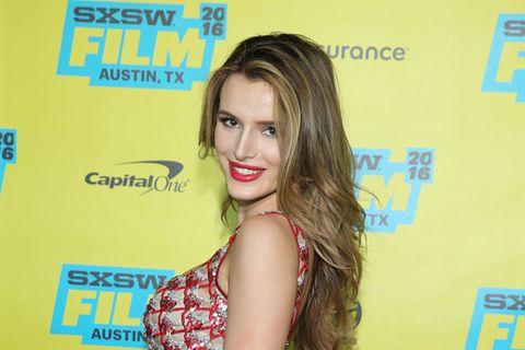 Nose, Hairstyle, Yellow, Eyelash, Style, Logo, Dress, Brown hair, Model, Tooth,