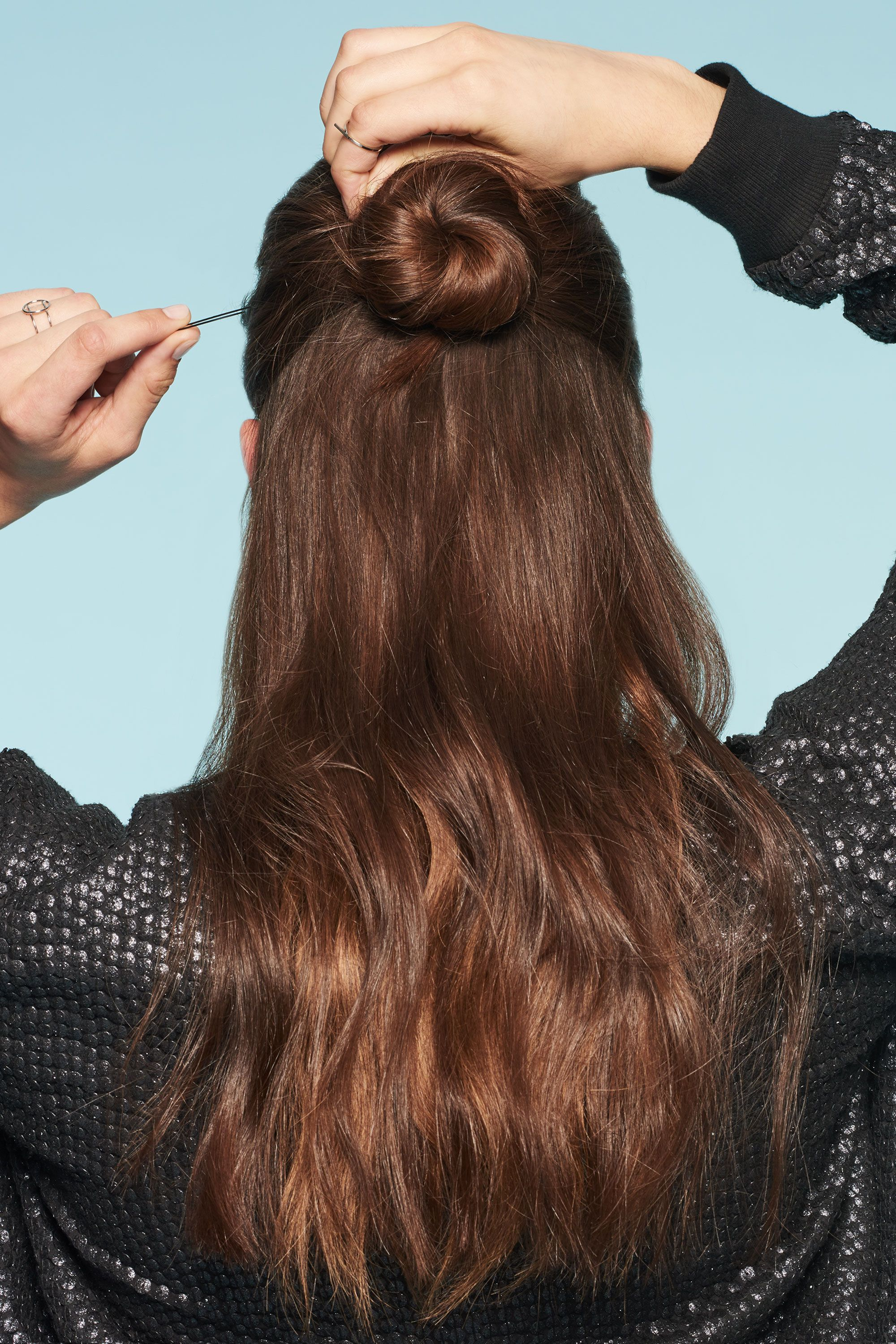 <p>Twist the ponytail and wrap it around the elastic to create a basic bun. Secure the ends with bobby pins, crisscrossing them for budge-free hold.</p>