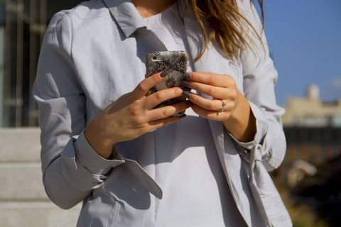 Woman with gray nails holding smartphone