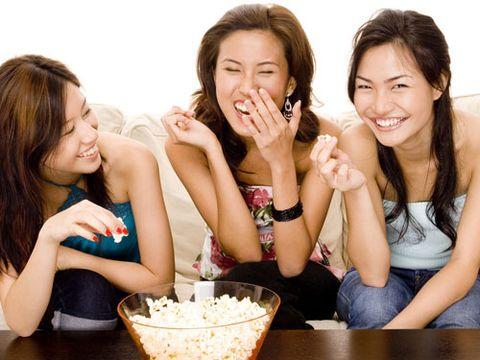 girls laughing around bowl of popcorn