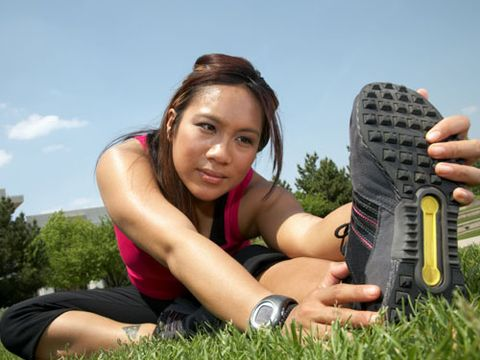 girl stretching on grass before exercising