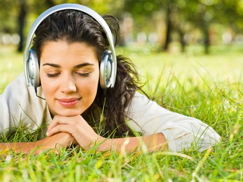 girl laying in the grass with head phones on looking calm