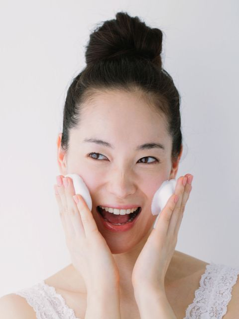 young woman washing face with foam