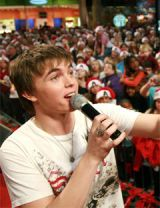 jesse mccartney singing into microphone in front of crowd