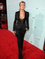 jennifer aniston walks down the red carpet in a black suit and gold necklace