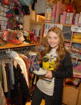 abigail breslin holding up a boot at a store