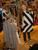abigail breslin holding up black and white dress at a store