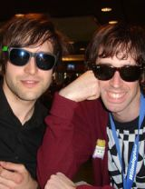 two smiling brown haired men wearing sunglasses in dining room
