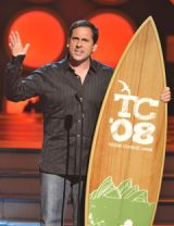 steve carrell ons tage holding a surfboard