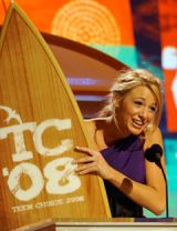 blake lively on stage holding a surfboard