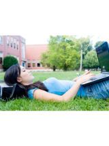 girl lying in grass with laptop