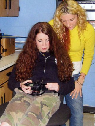 kesha wearing yellow sweater checking out a camera at her school