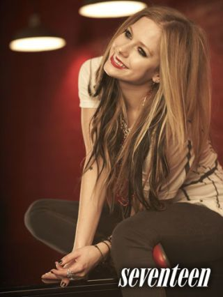 avril lavigne seated in white tee shirt and dark pants