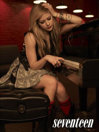 avril lavigne seated in a dress playing the piano