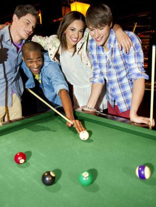 group of teenagers playing pool