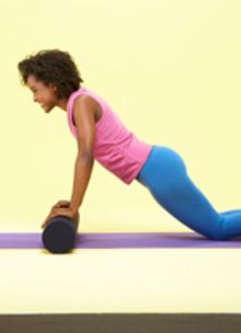 girl doing a push-up on a rolled mat wearing a pink shirt and blue pants
