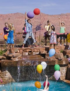 cast of high school musical performing in front of a pool
