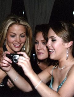 girls looking at pictures on a camera