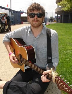 brown haired man in sunglasses and blue shirt playing guitar outside