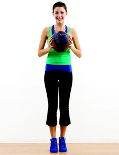girl standing and holding exercise ball in front of her chest