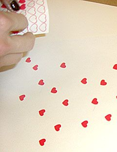 putting heart stickers on craft paper