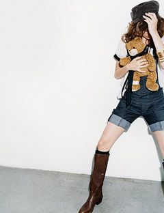 girl in denim shorts holding a teddy bear