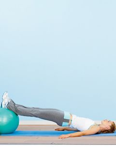 a girl stretched out with her legs elevated on an exercise ball