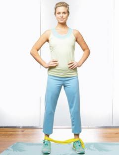 girl standing with hands on hips and resistance band around her ankles