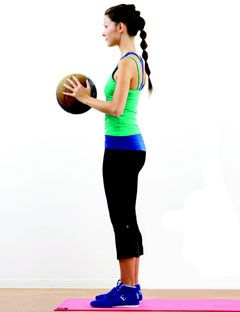 side view of girl standing and holding an exercise ball at chest level