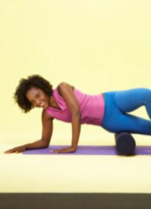 girl doing exercise on a rolled-up mat with a pink shirt and blue pants